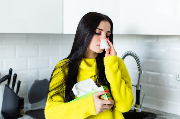 Sick young woman blows her nose in the kitchen.