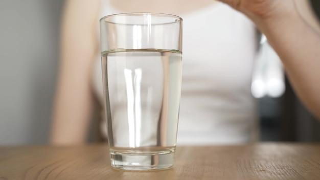 발포성 정제를 물 한 잔에 떨어뜨리는 아픈 젊은 여성.