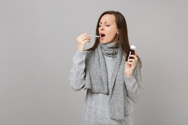 Sick young woman in gray sweater, scarf holding pour liquid medicine into spoon isolated on grey wall background. healthy lifestyle ill sick disease treatment, cold season concept. mock up copy space.