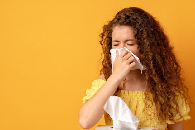 Больная молодая женщина, держащая тканевый носовой платок на желтом фоне
