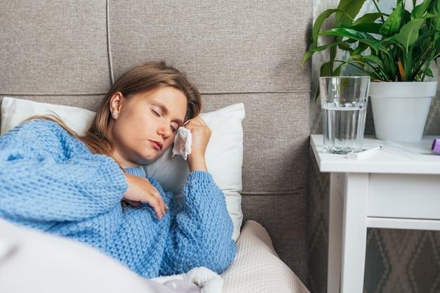 Больная молодая женщина в теплом свитере спит в постели под одеялом. головная боль, грипп, простуда, вирус.