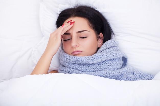 Больная молодая женщина кашляет на кровати
