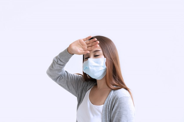 Sick young woman in medical face mask suffer in headache because of air pollution in the city building.