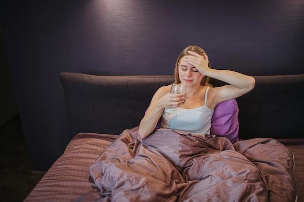 Больная молодая женщина сидит на кровати и держит одну руку на лбу