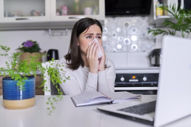 病気の若い女性。くしゃみとハンカチで咳、ホームオフィスでラップトップと一緒に座って、キッチンのインテリアの背景。ウイルス、季節風邪、アレルギー、インフルエンザシーズン