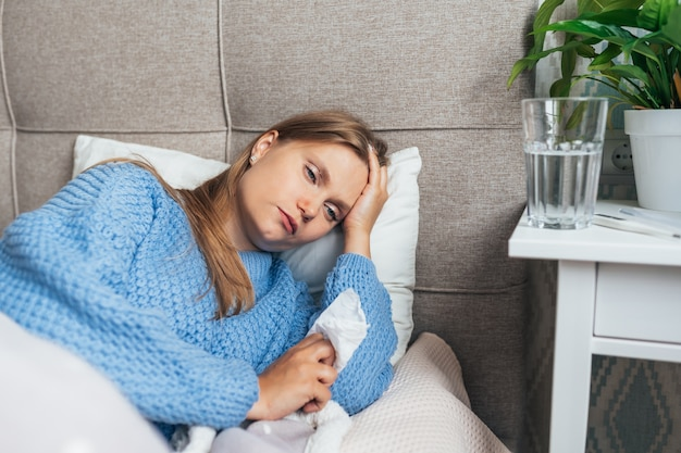 Sick young woman in warm sweater rest in bed under blanket.