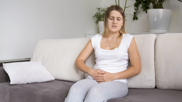 Sick young woman with abdominal or stomach pain sitting on sofa in living room