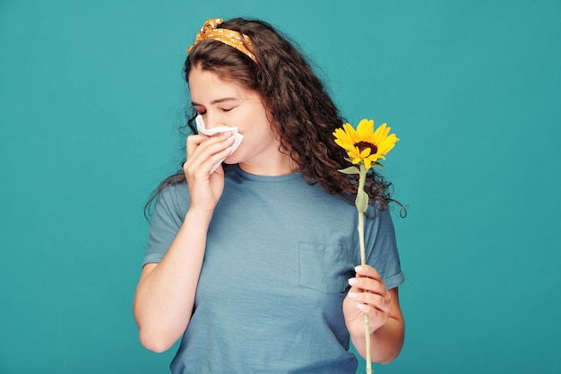 Sick young woman with handkerchief blowing her nose while holding sunflower in front of herself over blue wall