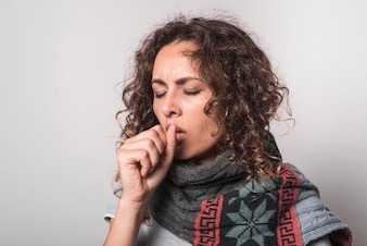 Sick young woman with scarf around her neck coughing
