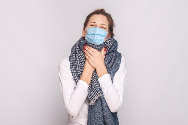 외과용 의료용 마스크와 파란색 스카프를 쓴 아픈 젊은 여성은 기분이 좋지 않고 목이 아프다. 실내, 스튜디오 촬영, 회색 배경에 고립