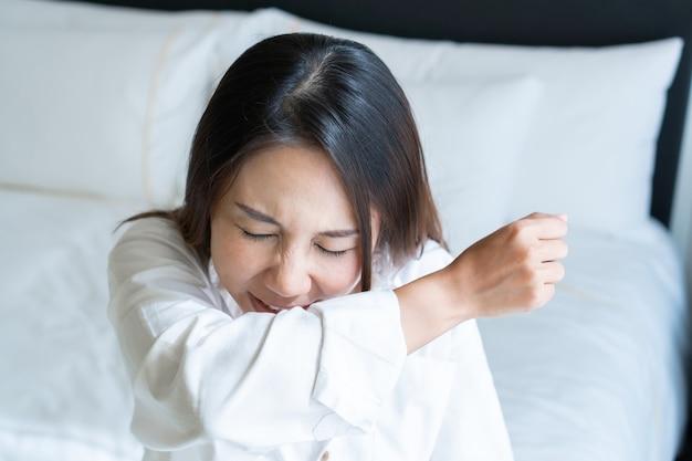 目覚めた後、ベッドルームで彼女の肘にくしゃみをする病気のアジア人女性