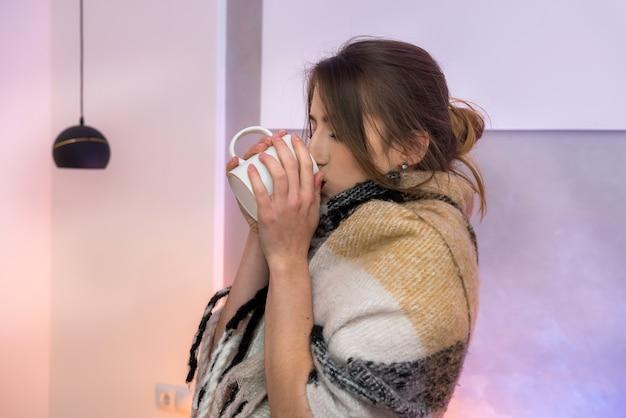 질병 개념입니다. 매우 슬픈 감정으로 포즈를 취하는 따뜻한 담요와 뜨거운 찻잔을 가진 여자