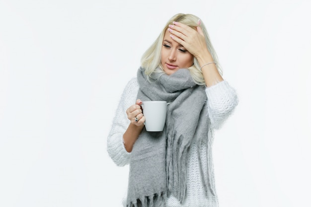 Шарф больной милой молодой белокурой женщины обернутый имея головную боль, касаясь ее виску и закрытым глазам, крупному плану. простуда, вирус, мигрень, концепция сезона гриппа.