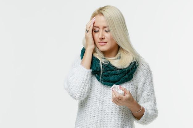 病気のかわいい若いブロンドの女性は、頭痛を持っているスカーフを包み、彼女の寺院に触れ、目を閉じて、クローズアップ。風邪、ウイルス、片頭痛、インフルエンザシーズンコンセプト。