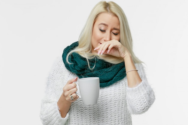 Sickness cute young blonde woman wrapped scarf having headache, touching her temple and closed eyes, closeup. cold, virus, migraine, flu season concept.
