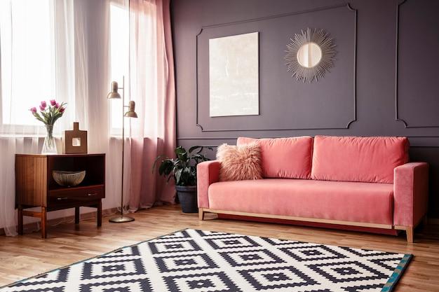 パウダーピンクのソファ、模様入りのラグ、木製キャビネット、壁の装飾が施されたリビングルームのインテリアのサイドアングル