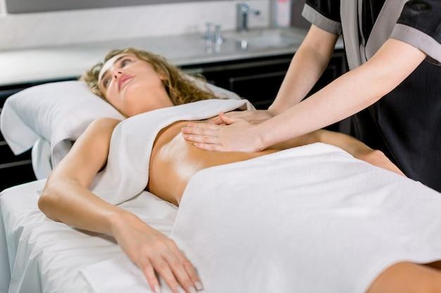 女性の腹部をマッサージする手の側面の角度のビュー。セラピストがお腹に圧力をかけます。スパサロンで手動マッサージを受けるかなり若いブロンドの女性