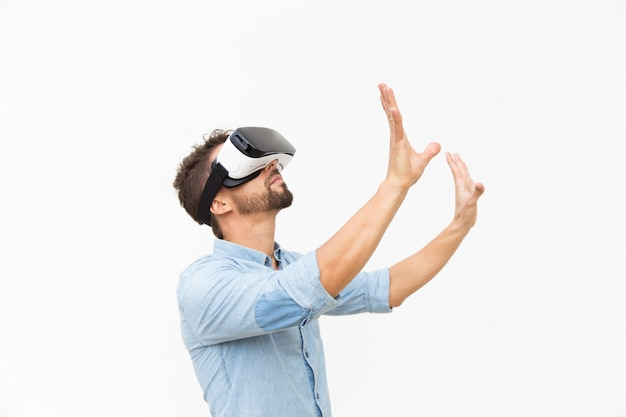 Side of bearded guy wearing vr goggles, touching air