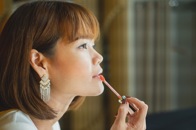 Side of beautiful young woman putting on red lipstick gloss.