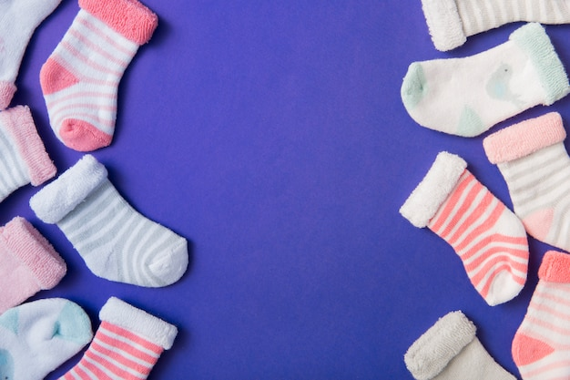 Side border made with different type of baby's sock on blue background