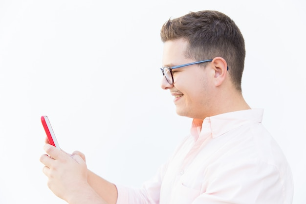 Side of cheerful guy in eyeglasses texting message