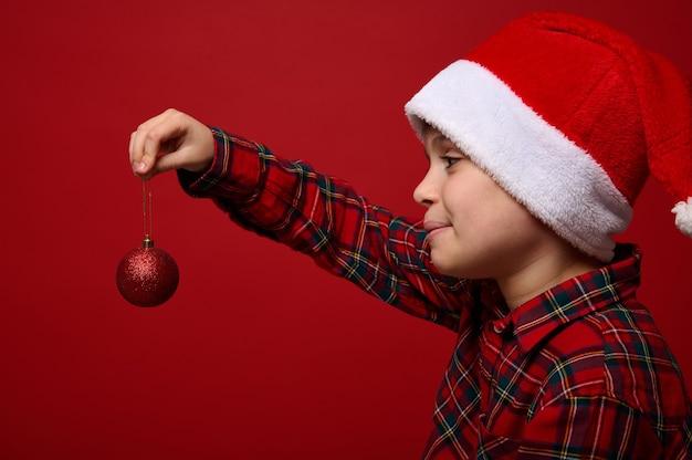 Боковой крупным планом портрет красивого мальчика в шляпе санта-клауса, держащего перед собой красную блестящую сферическую игрушку елки, позирующего на цветном фоне с копией пространства для новогодней рекламы