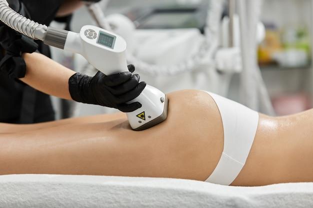 Боковой снимок руки косметолога в черных перчатках, делающей антицеллюлитный массаж женских ягодиц с профессиональным устройством