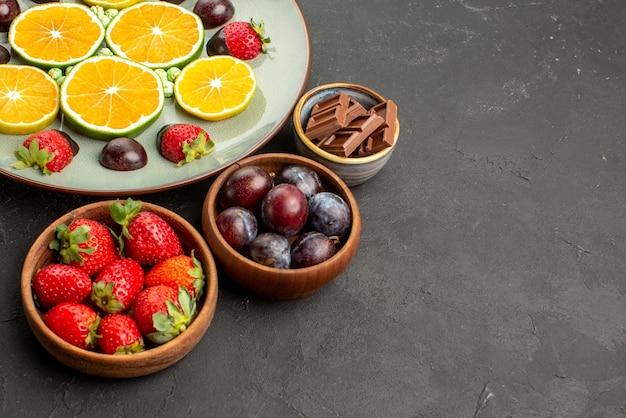 흰색 접시에 초콜릿으로 덮인 딸기와 잘게 썬 오렌지의 측면 클로즈업 과자와 초콜릿 접시, 테이블 왼쪽에 초콜릿과 딸기 그릇