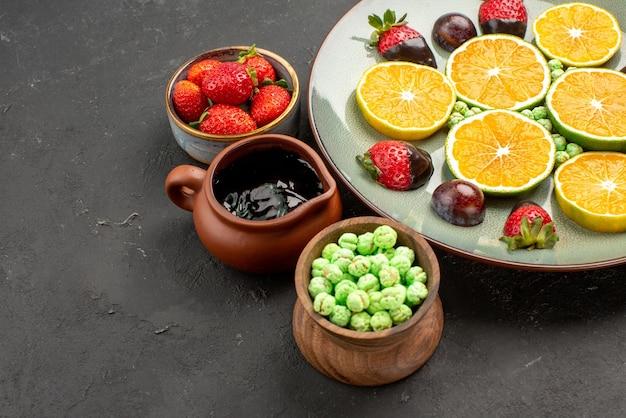 Боковой крупный план сладостей и шоколадная тарелка с клубникой в шоколаде и нарезанным апельсином на белой тарелке и миски с шоколадным соусом, конфетами и ягодами на правой стороне стола