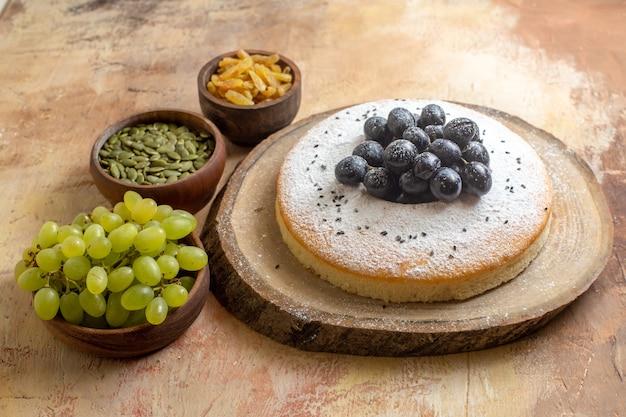 Вид сбоку крупным планом торт торт на доске зеленый виноград изюм тыквенные семечки в мисках