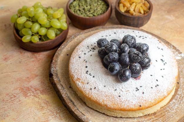Вид сбоку крупным планом торт торт на доске изюм зеленый виноград тыквенные семечки
