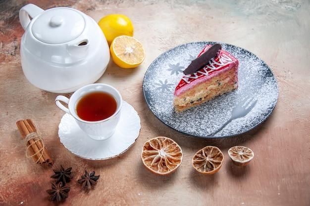 측면 확대보기 케이크 케이크 주전자 레몬 계피 스틱 흰색 차 한잔