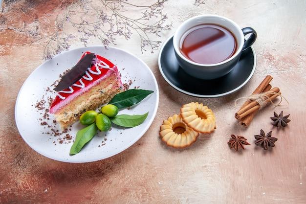 Вид сбоку крупным планом торт чашка чая торт лимонное печенье звездчатый анис палочки корицы