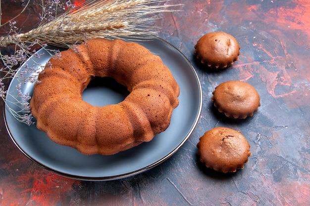 側面のクローズアップは、ケーキ小麦の耳のカップケーキと木の枝のケーキプレートを表示します。