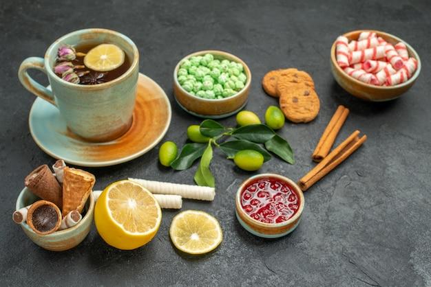 側面のクローズアップビューお茶のカップお茶のクッキーキャンディーワッフル柑橘系の果物シナモン
