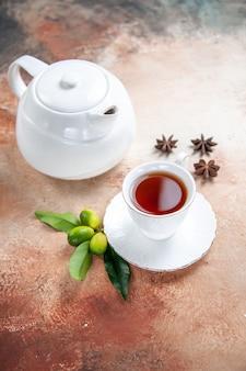 側面のクローズアップビューお茶の白いティーポットのカップお茶の柑橘系の果物のスターアニスのカップ