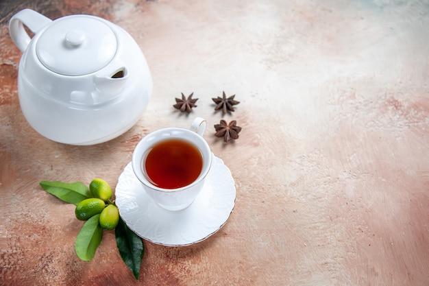 Вид сбоку крупным планом чашка чая белый чайник чашка чая звездчатый анис цитрусовые