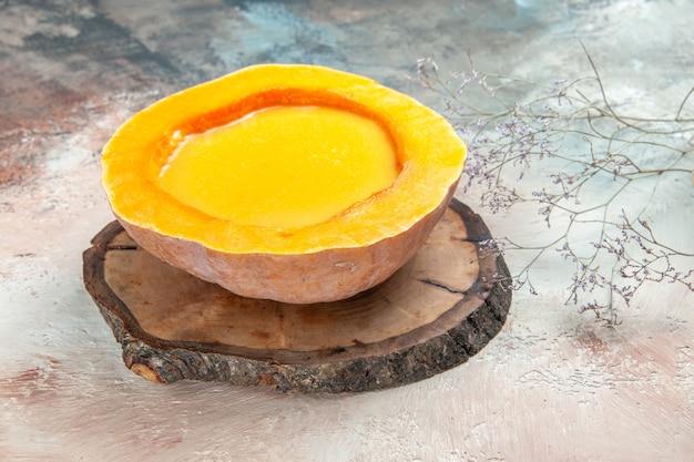 側面のクローズアップは、テーブルの上の木の板のカボチャのスープのスープを表示します