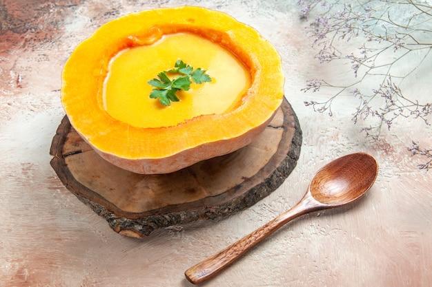 Боковой вид сверху суп из тыквы на доске рядом с ветками дерева ложка