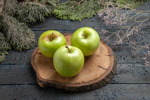 Vista ravvicinata laterale mele appetitose mele verdi su tavola di legno tra rami di alberi e rami di abete rosso