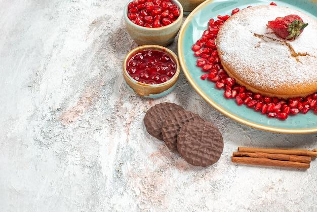 Vista ravvicinata laterale la torta appetitosa la torta appetitosa accanto alle ciotole di biscotti al cioccolato