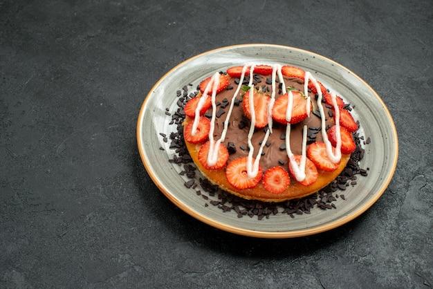 側面のクローズアップビュー食欲をそそるケーキ黒いテーブルの中央のプレートにイチゴとチョコレートの食欲をそそるケーキ