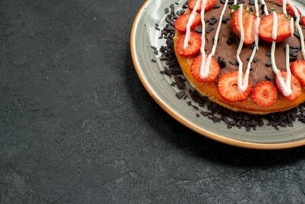 검정 테이블 오른쪽에 있는 흰색 접시에 딸기 조각과 초콜릿을 넣은 맛있는 케이크 맛있는 케이크 측면 클로즈업