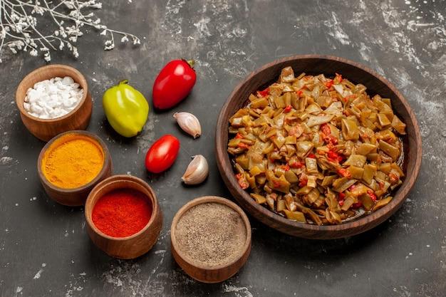 Vista ravvicinata laterale piatto appetitoso piatto appetitoso di fagiolini accanto alle ciotole di spezie colorate pomodori aglio e pepe sul tavolo scuro