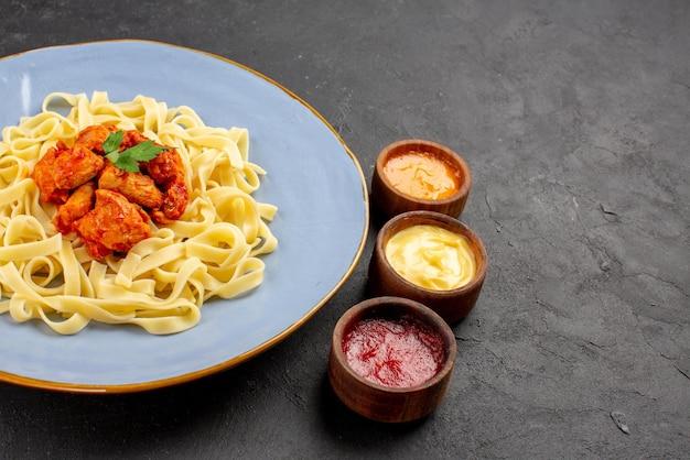 Vista ravvicinata laterale piatto appetitoso piatto blu di pasta carne e sugo accanto alle salse colorate sul lato sinistro del tavolo