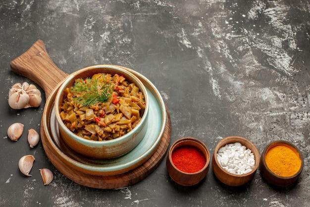 にんにくの横にあるスパイスの食欲をそそる皿ボウルと黒いテーブルのまな板に食欲をそそるインゲンとトマトの側面のクローズアップビュー