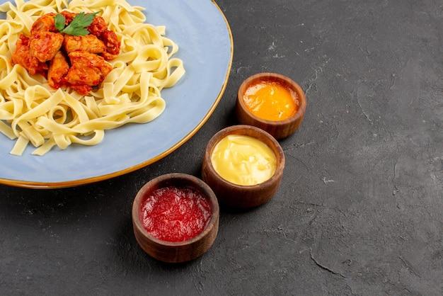 Боковой вид крупным планом аппетитное блюдо блюдо из пасты, подливки и мяса в синей тарелке рядом с красочными соусами на темной поверхности