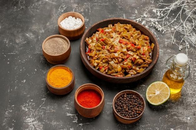 Vista ravvicinata laterale piatto appetitoso cinque ciotole di spezie bottiglia di olio e un piatto appetitoso accanto ai rami degli alberi sul tavolo scuro