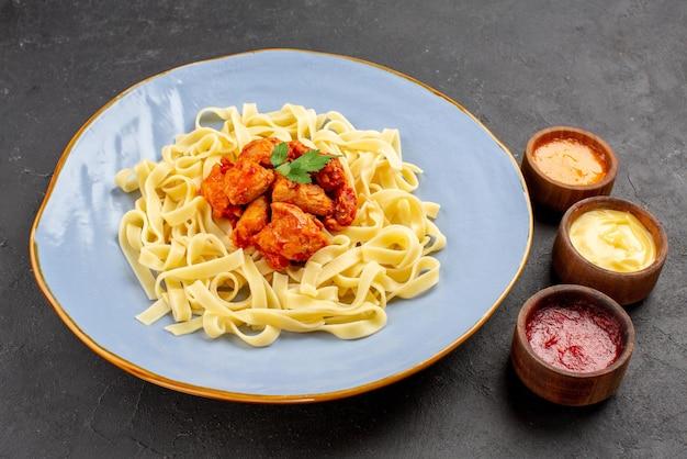 テーブルの上のカラフルなソースの横にある青いプレートの食欲をそそる料理のパスタ肉とグレービーの側面のクローズアップビュー