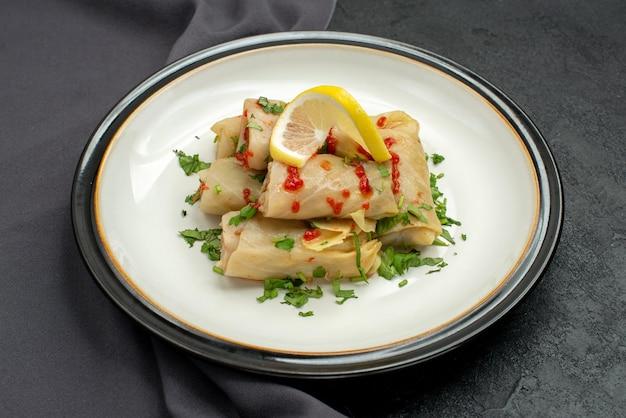 Боковой вид крупным планом аппетитное блюдо из голубцов с лимонными травами и соусом на серой скатерти в центре темного стола